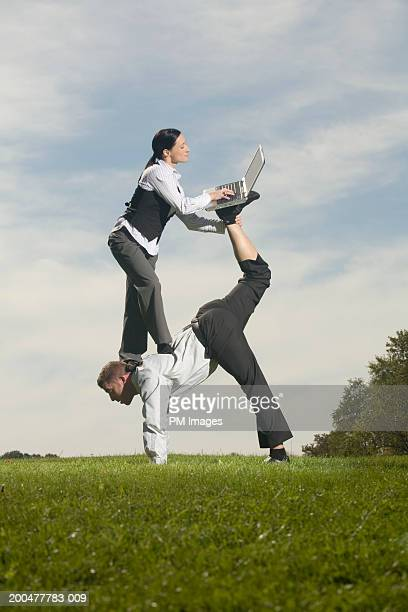 Businesswoman balancing on man's back, using laptop, side view