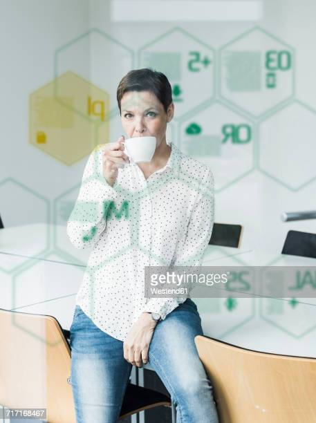 Businesswoman behind glass pane with data in office