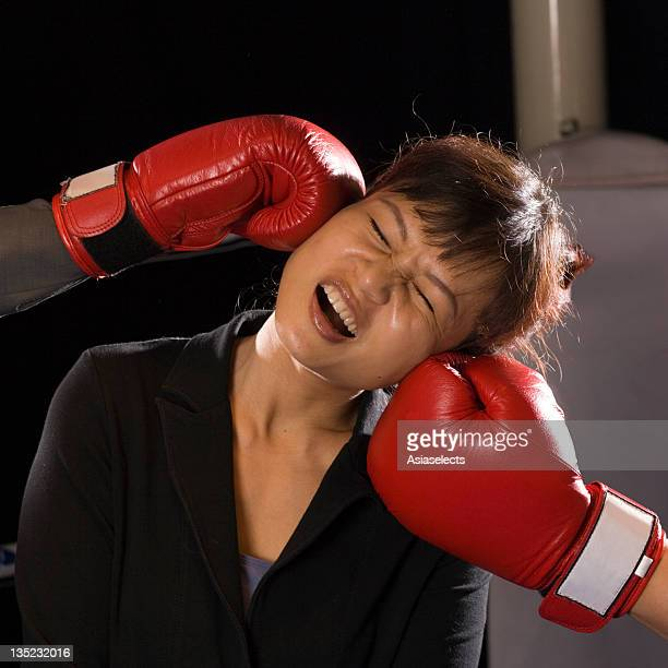 Businesswoman being hit by two opponents