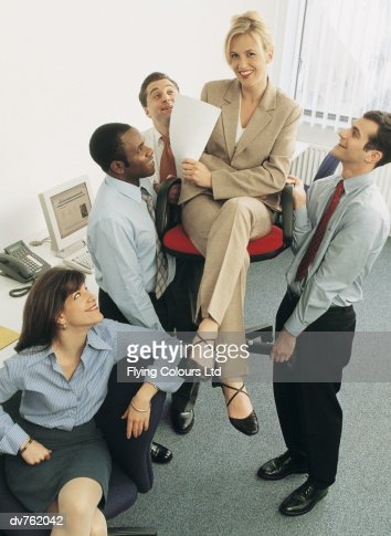 Businesswoman Being Lifted in a Chair by Her Colleagues