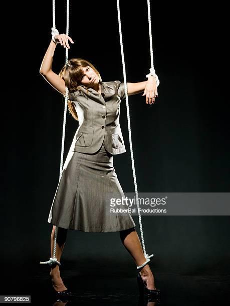 Mulher de Negócios sendo empurrado por cadeias de caracteres como um Fantoche