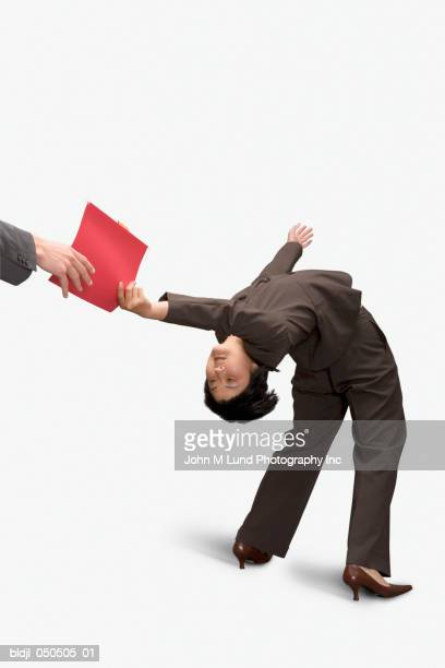 Businesswoman bending over backward and handing a file
