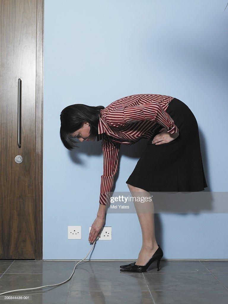 Businesswoman bending to reach plug socket
