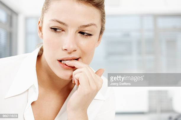 Businesswoman biting fingernails