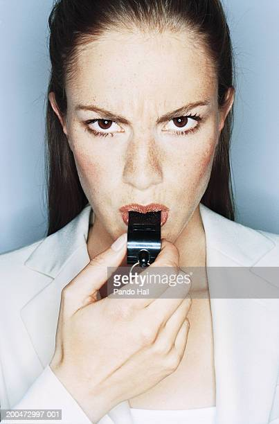 Businesswoman blowing whistle, portrait, close-up