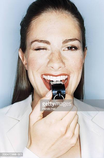 Businesswoman blowing whistle, winking, close-up