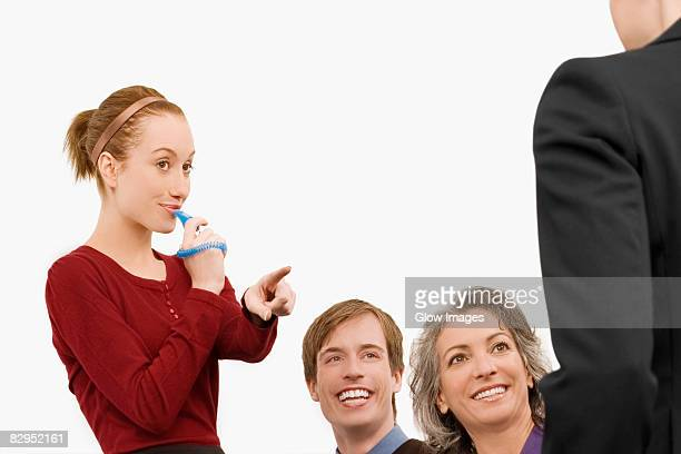 Businesswoman blowing whistle with three business executives beside her