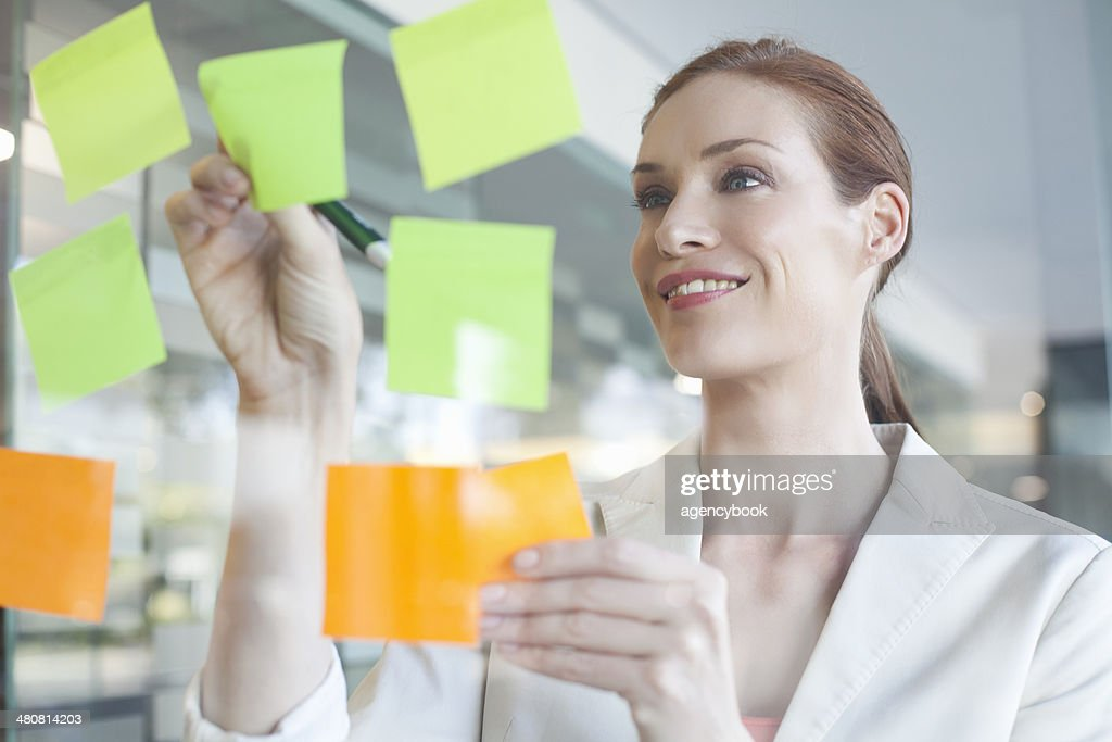 Businesswoman brainstorming using sticky notes