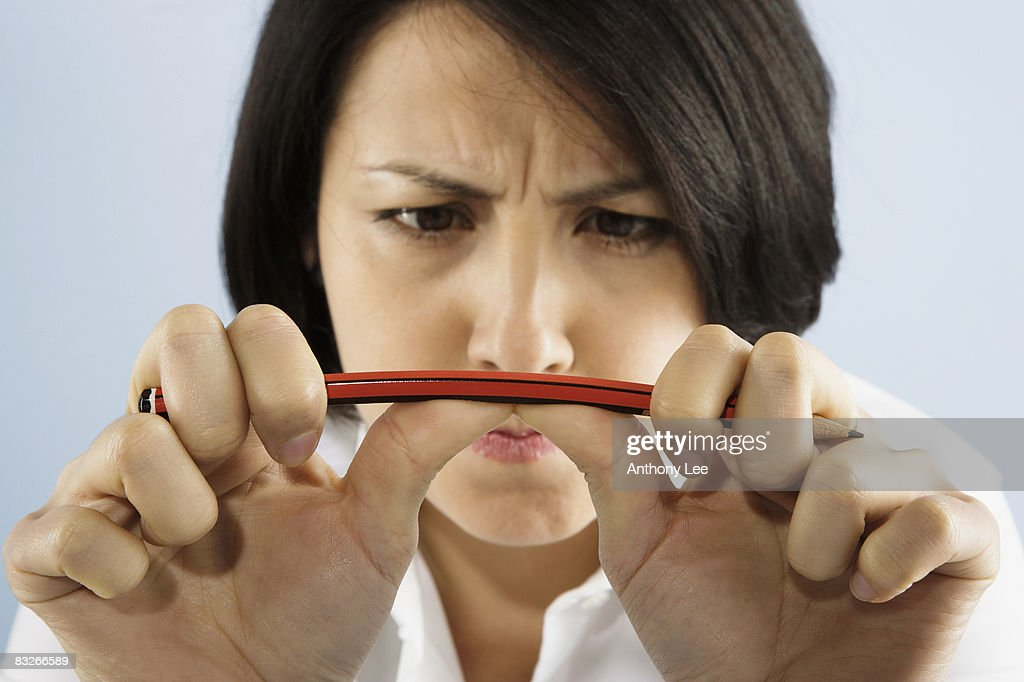Businesswoman breaking pencil : Stock Photo