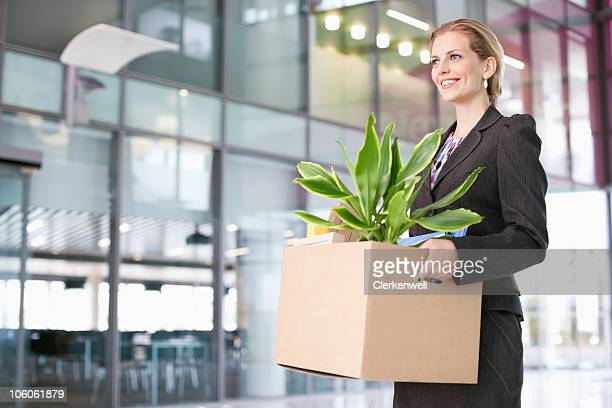 Businesswoman carrying a cardboard box with a potted plant
