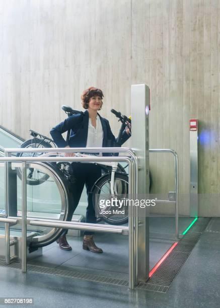 businesswoman carrying bike at subway station, using escalator