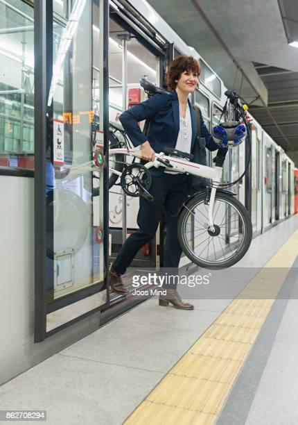 businesswoman carrying bike, leaving subway train