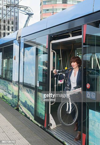 businesswoman carrying bike, leaving train