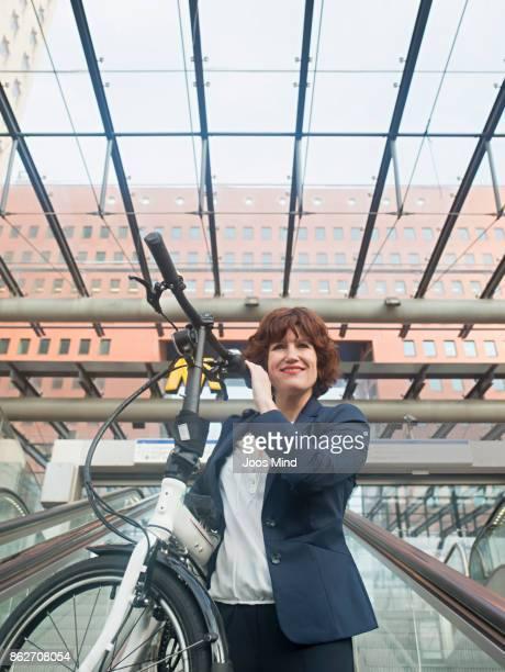businesswoman carrying bike on shoulder, using escalator to subway