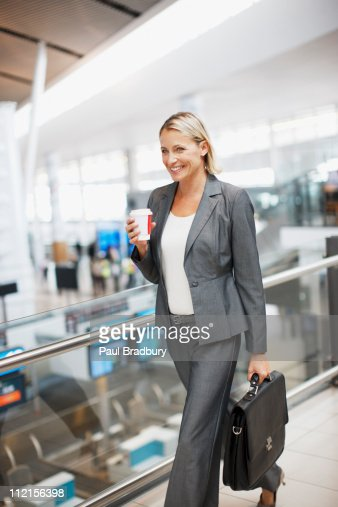 Businesswoman carrying coffee in airport : Stock Photo