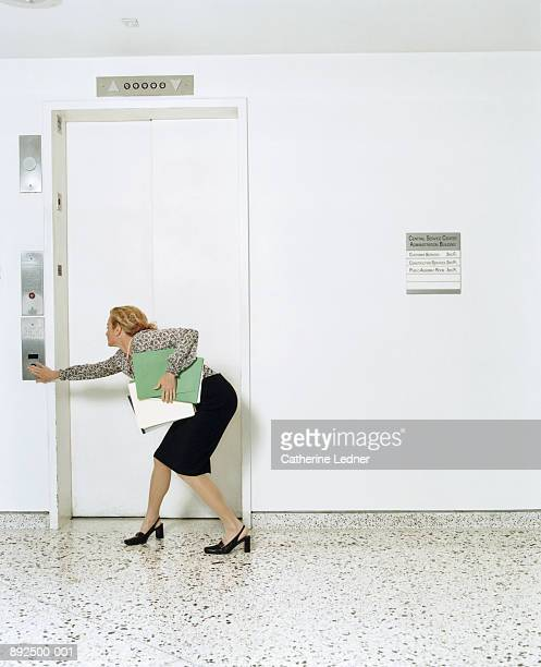 Businesswoman carrying files, pushing elevator button