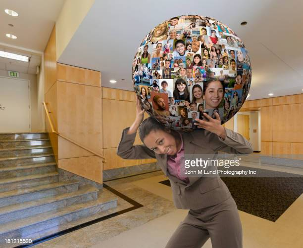 Businesswoman carrying globe on her back