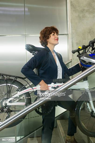 businesswoman carrying her folding bike up stairway