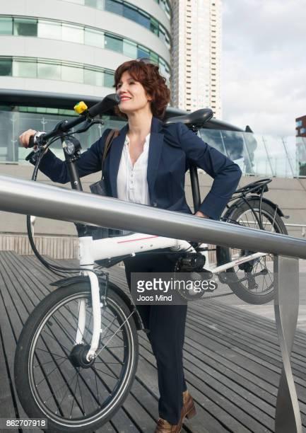 businesswoman carrying her folding bike upstairs