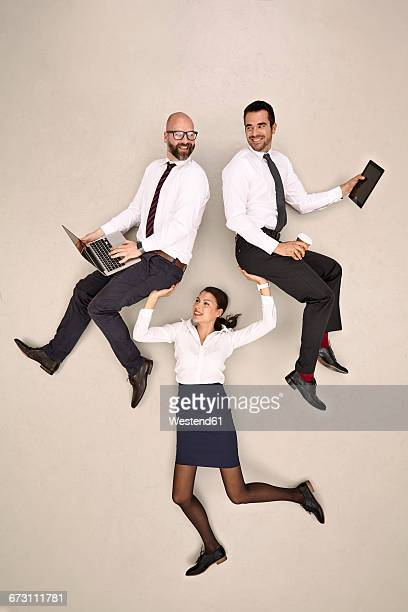 Businesswoman carrying her two male colleagues