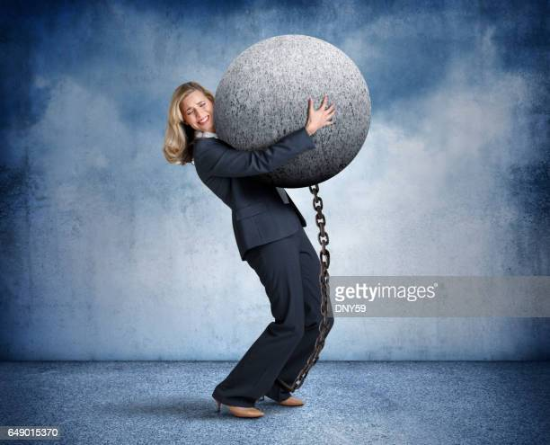 Businesswoman Carrying Large Ball And Chain