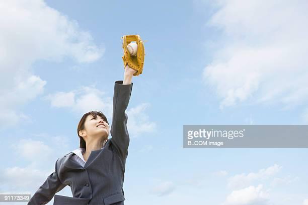 Businesswoman catching ball