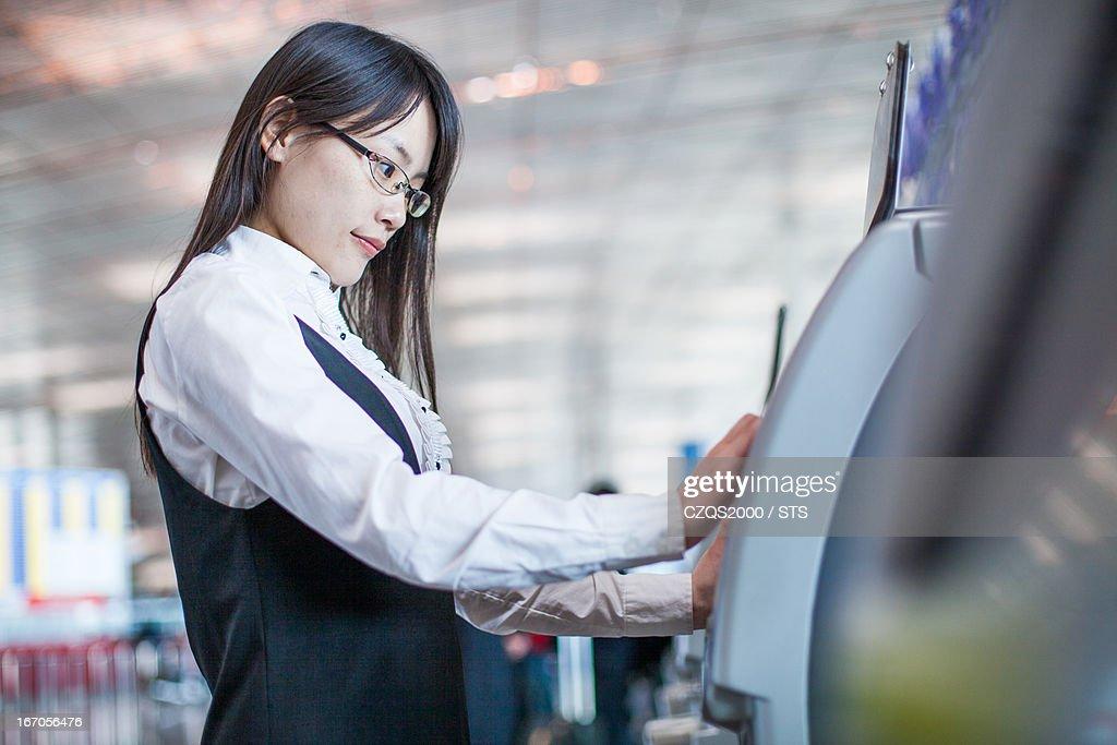 Businesswoman check in by auto check in machine