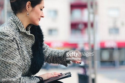 Businesswoman checking her hand watch and waiting for transport