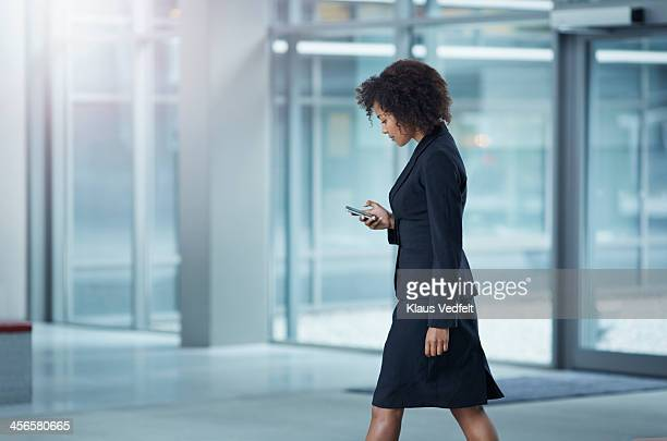 businesswoman checking her phone, while walking