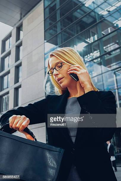 Businesswoman checking time while talking on cell phone outside office building