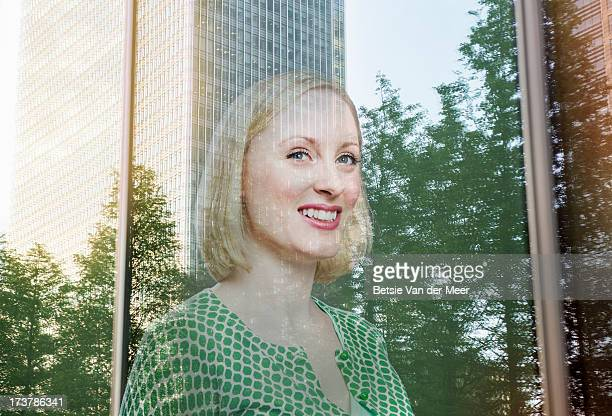 Businesswoman, city and trees reflected in window.