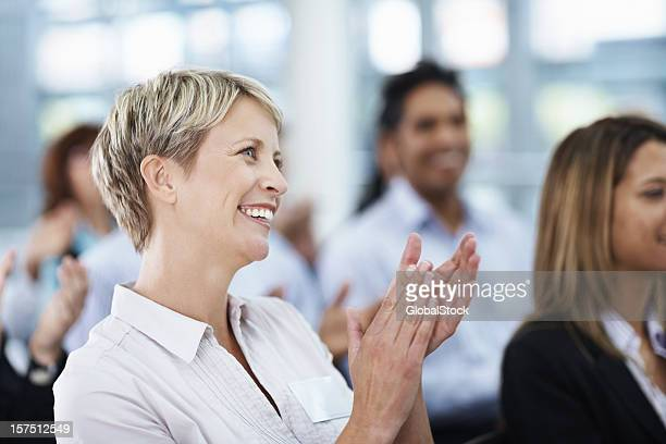 Businesswoman clapping at seminar