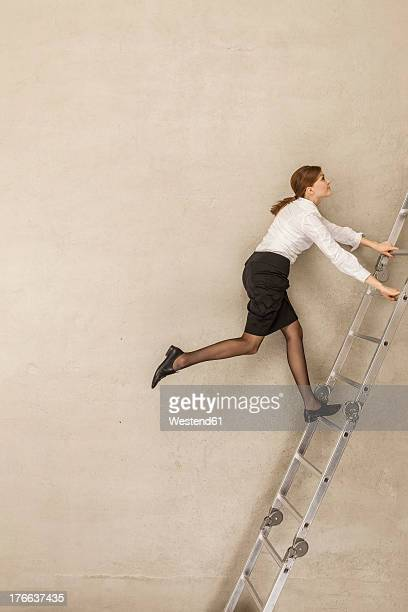 Businesswoman climbing ladder in office