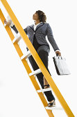 African-American businesswoman holding briefcase and climbing yellow ladder.