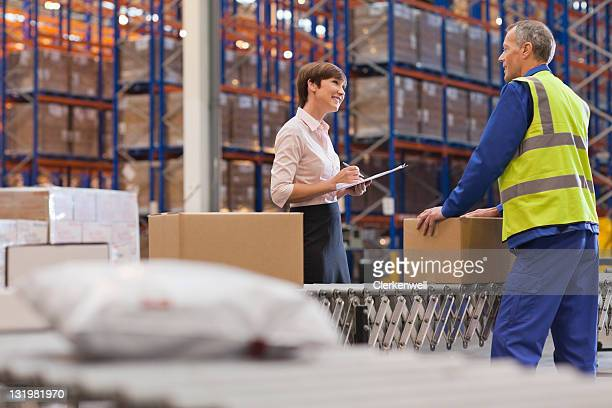 Businesswoman clipboard discussing with mature male warehouse worker
