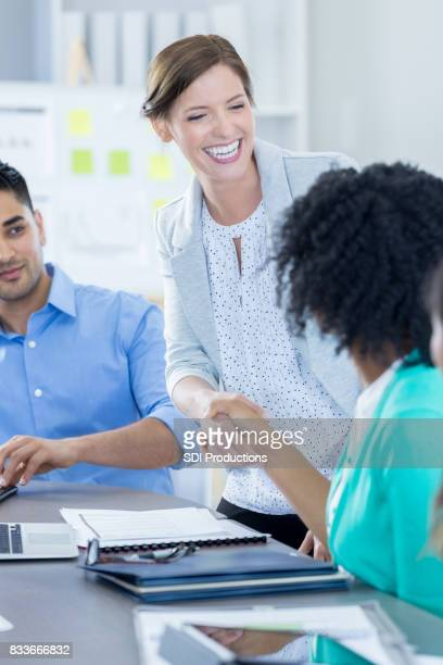 Businesswoman congratulates colleague after successful presentation