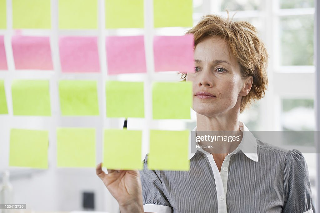 A businesswoman considering rows of adhesive notes on glass : Stock Photo