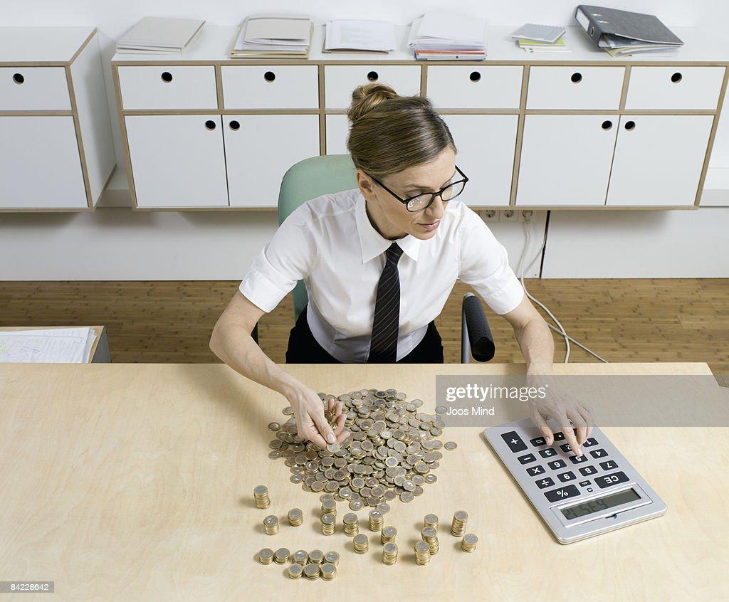 businesswoman counting money, using calculator : Stock Photo
