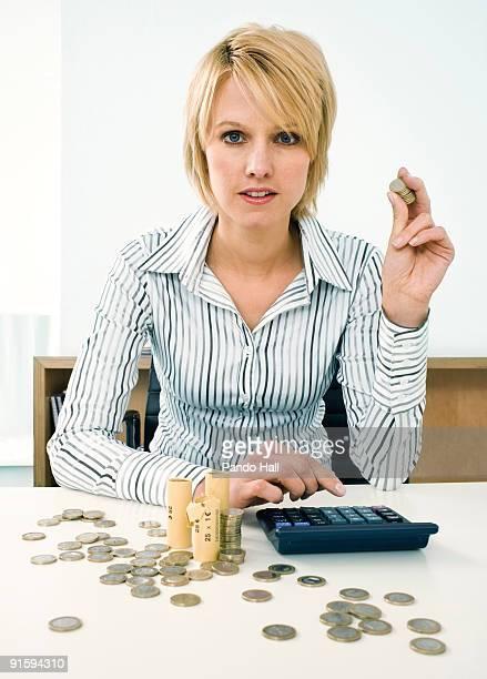 Businesswoman counting money, using calculator