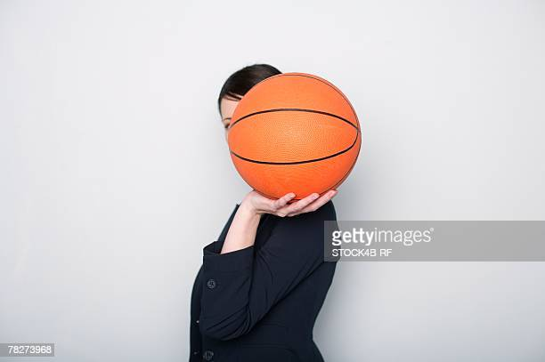 Businesswoman covering face with a basketball
