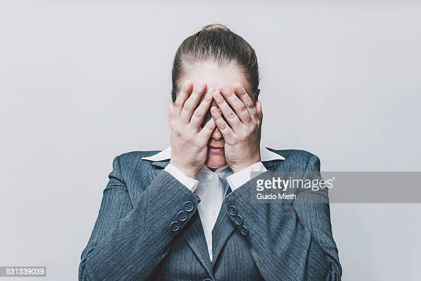 Businesswoman covering her face.