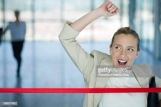 Businesswoman crossing finishing line
