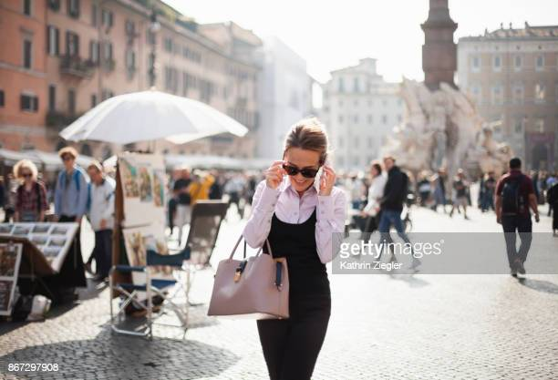 Businesswoman crossing Piazza Navona in Rome, talking on mobile phone