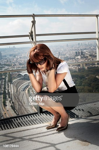 Businesswoman Crouching on Roof and Rubbing Temples : Stock Photo