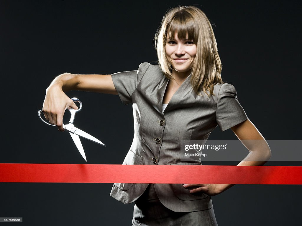 businesswoman cutting a red ribbon