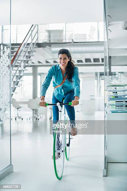 Businesswoman cycling inside office