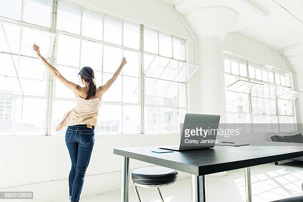 Businesswoman dancing by office window