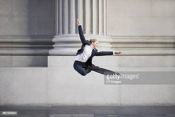 Businesswoman dancing in urban setting
