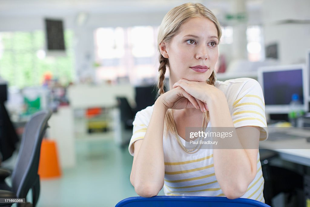Businesswoman daydreaming in office : Stock Photo