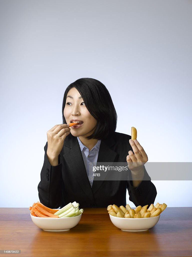 Businesswoman deciding what to eat : Stock Photo